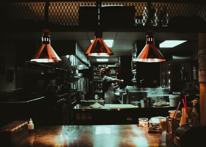 σκοτεινή λήψη γυναίκας που δουλεύει σε κουζίνα εστιατορίου